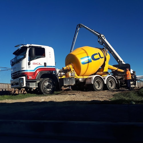 Side profile of an ACL Concrete Mixer and a worker operating the dispensing arm
