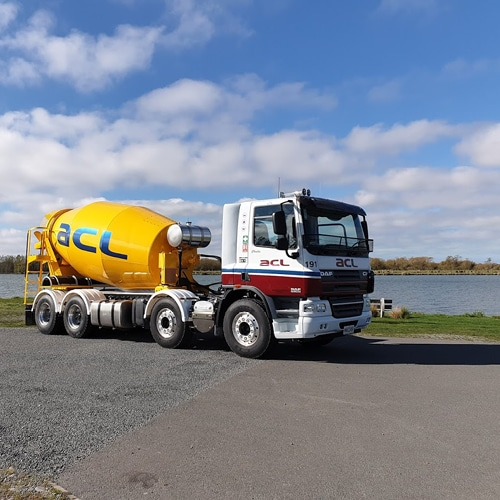 Side profile of an ACL Concrete Mixer parked in front of a lake