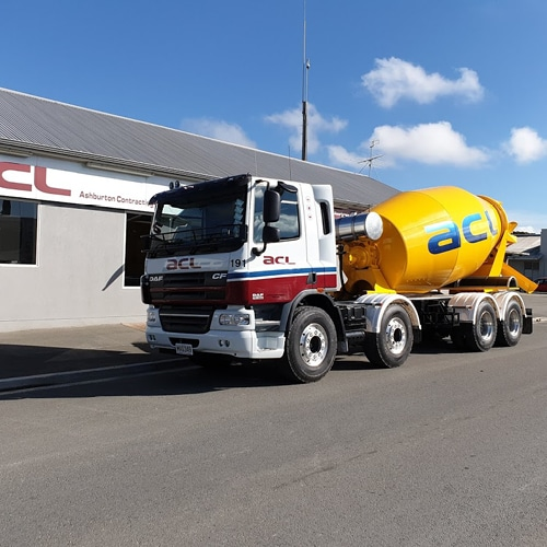 Side profile of a ACL Concrete Mixer parked outside a building